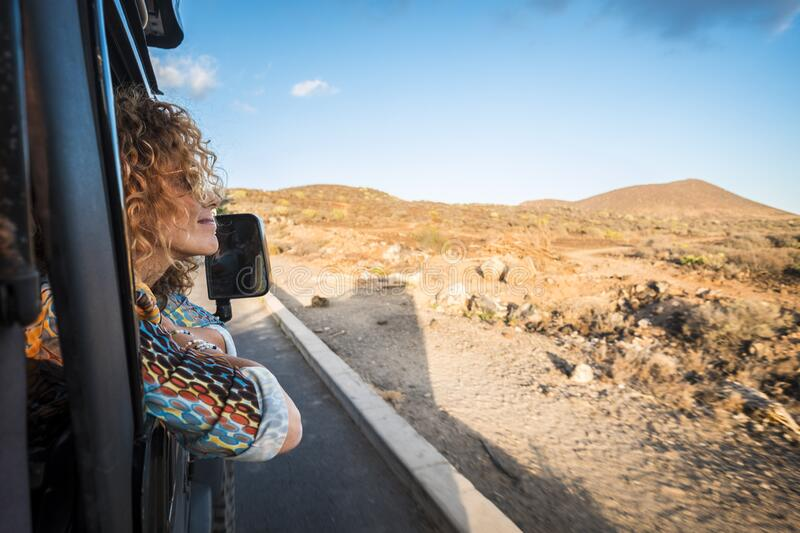 Beautiful caucasian young woman traveling with an off road black car and looking outside the landscape. desert and mountains royalty free stock photos