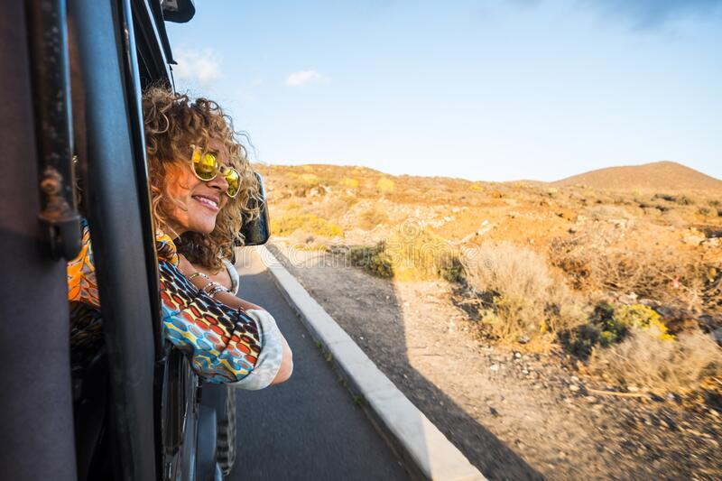 Beautiful caucasian young woman traveling with an off road black car and looking outside the landscape. desert and mountains stock image