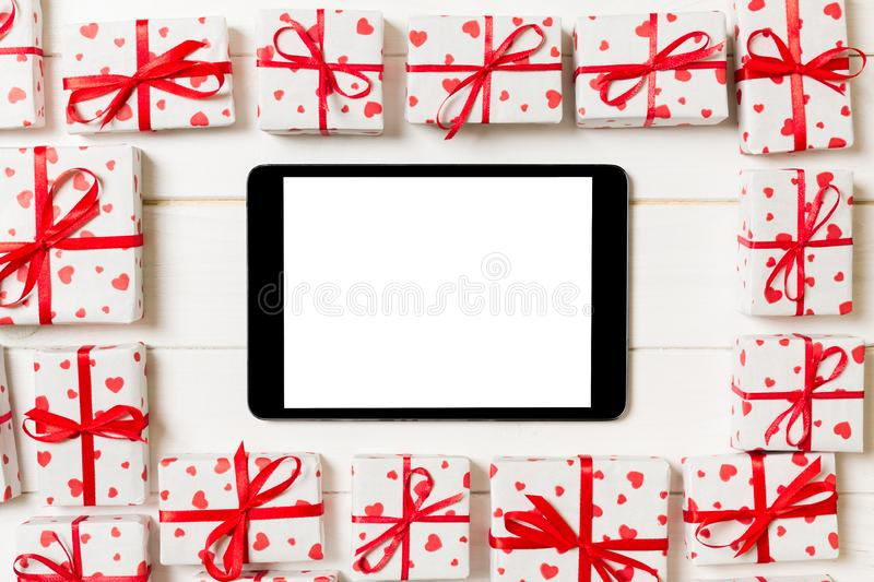 Beautiful celebratory valentine day or other holidays background. tablet with blank screen on the wooden background. Digital stock image