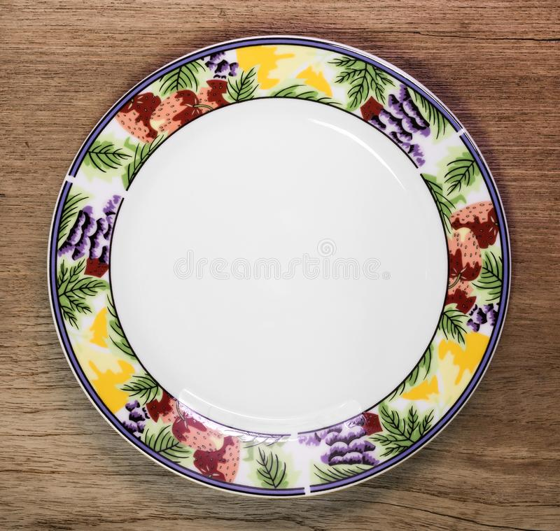 Beautiful ceramic dish on wooden table background. Design plate in fruit pattern style. Dish royalty free stock photography