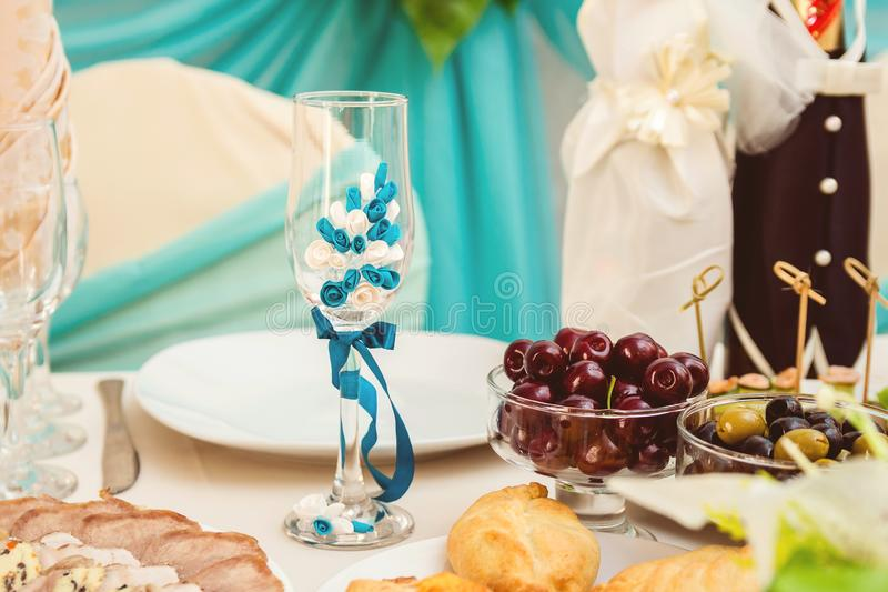 Beautiful champagne glass decorated with blue flowers. Wedding champagne royalty free stock photography