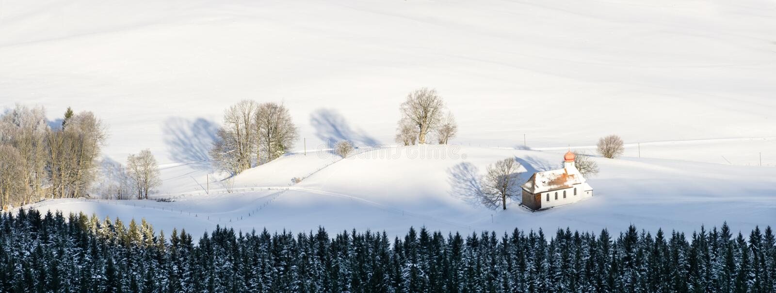 Beautiful chapel in lovely rural countryside on snowy winter sunrise seen from above. Weitnau, Allgau, Bavaria, Germany. royalty free stock images