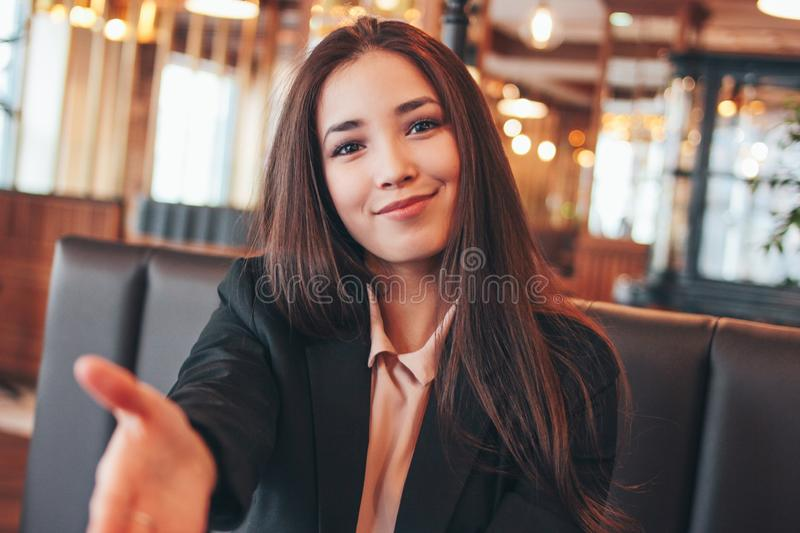 Beautiful charming brunette happy asian girl young woman giving handshake, hand of help, greeting at cafe stock images