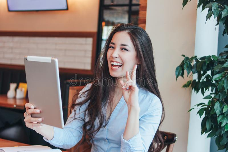 Beautiful charming brunette smiling Asian girl speaking or studying something on tablet at cafe royalty free stock photo