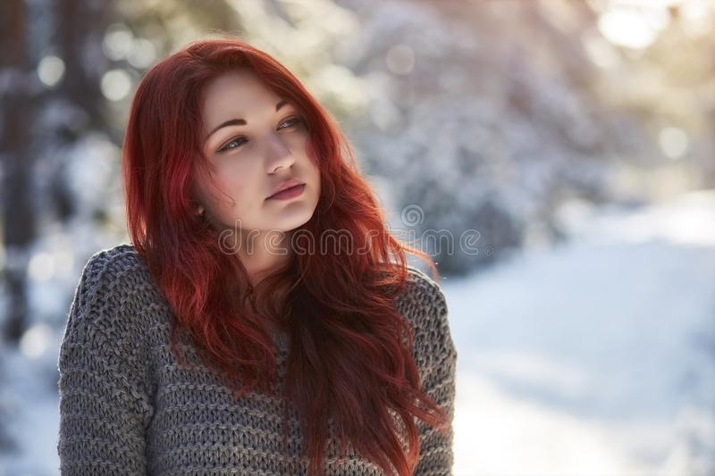 Beautiful charming girl with red hair in the winter park. Pensive, dreamy, loving look. Cold weather. stock photo