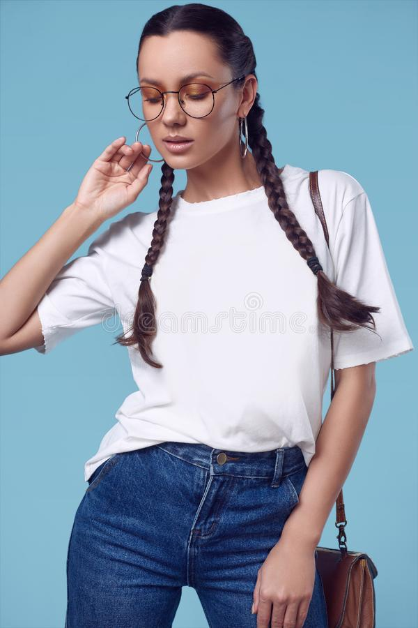 Beautiful charming hispanic girl in white t-shirt, jeans and glasses. Glamorous fashion portrait of beautiful charming hispanic girl in white t-shirt, jeans and stock photography