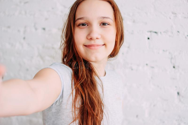 Beautiful charming redhead smiling teenager girl taking selfie on frontal camera isolated on white brick wall stock image