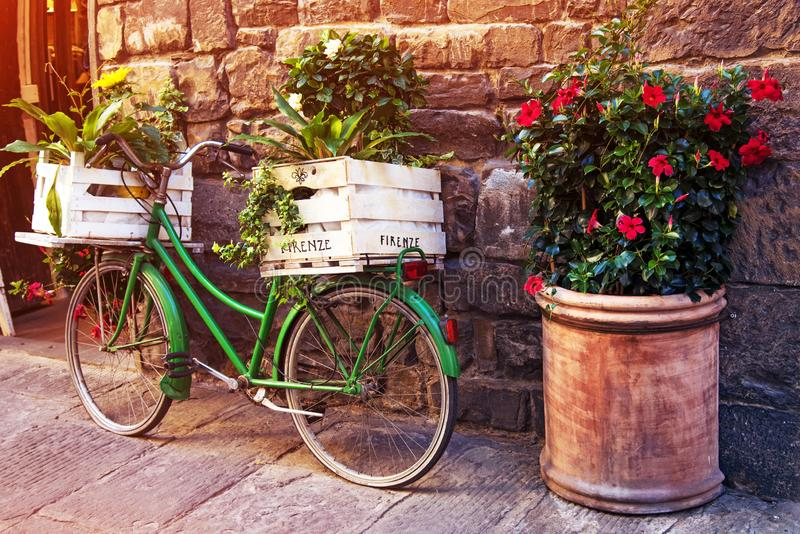 Beautiful charming street landscape with an old bike with flowers in boxes in the middle of an ancient street on a cobblestone stock image