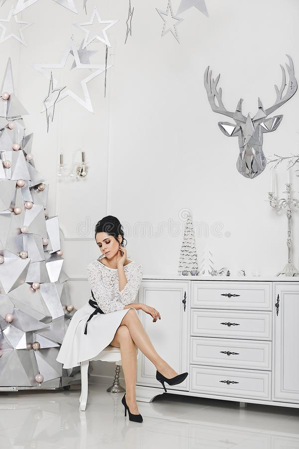 Beautiful charming woman with sexy legs in short dress posing in luxurious apartments decorated for New year. Model girl. In trendy outfit posing against silver stock image