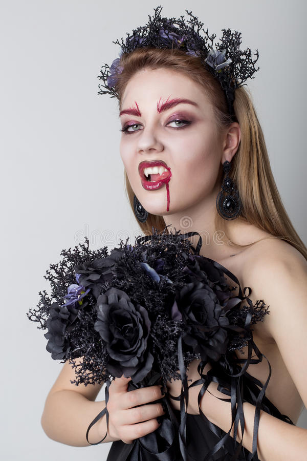 Beautiful cheeky girl in the image of a vampire with bright dark makeup, black vampire bride with a bouquet and a black wreath royalty free stock photos