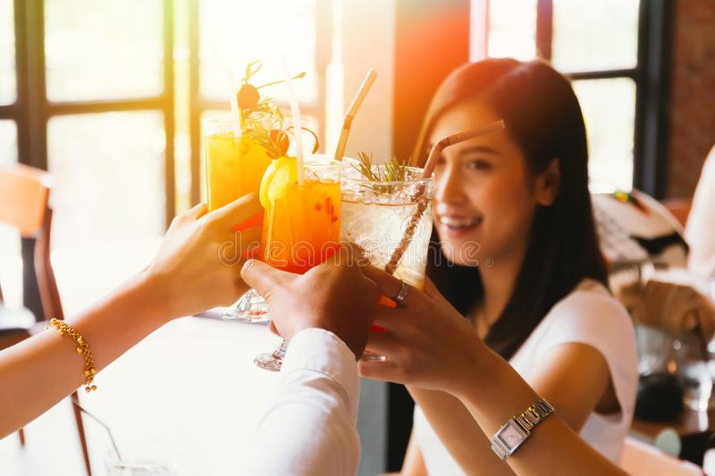 Beautiful and cheerful Asian woman cheering up for toast and celebration with friends in bar stock images