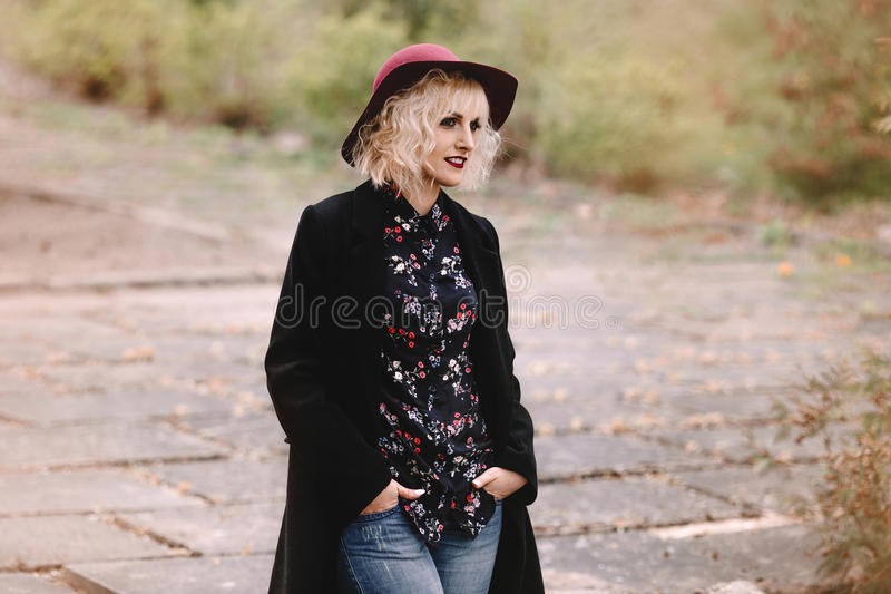 Beautiful cheerful blonde girl with short curly hair in coat and hat walking outdoors on stairs stock photography
