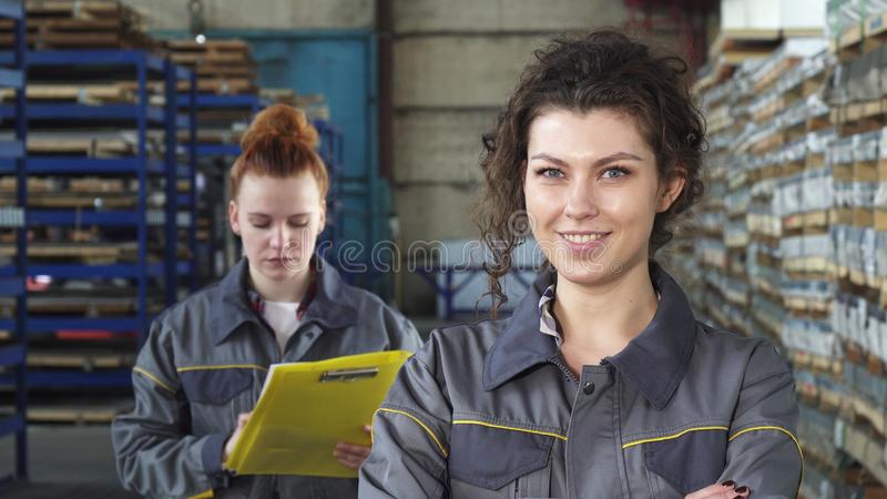 Beautiful cheerful female factory worker smiling to the camera royalty free stock image