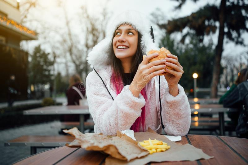 Beautiful and cheerful girl eating a juicy hamburger and french fries on the street stock images