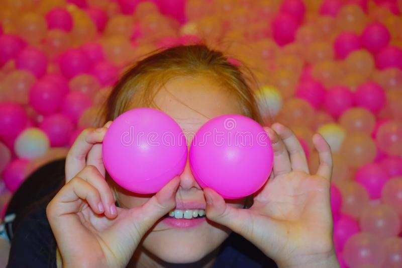 Beautiful cheerful girl with pink bright plastic balls. Pool with multi-colored balls royalty free stock photography