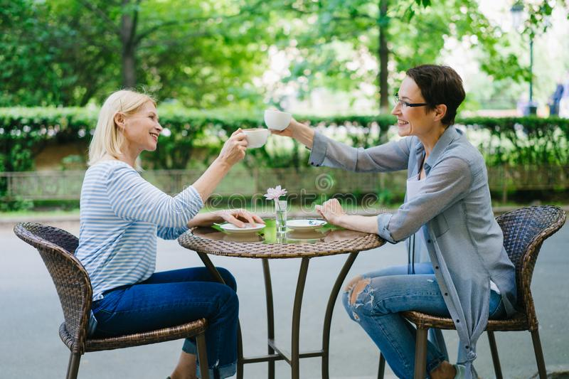 Beautiful cheerful ladies clanging tea cups talking in outdoor cafe royalty free stock photography