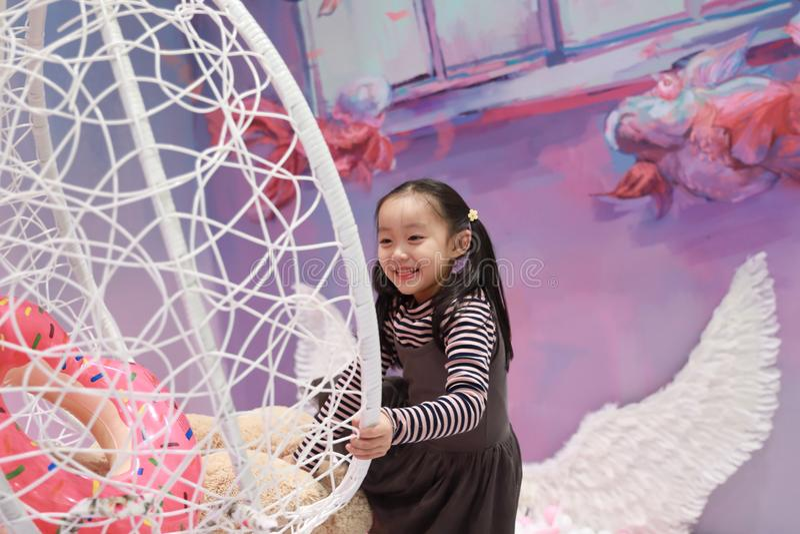 Beautiful cheerful little girl playing pleasure ground on playground royalty free stock photo