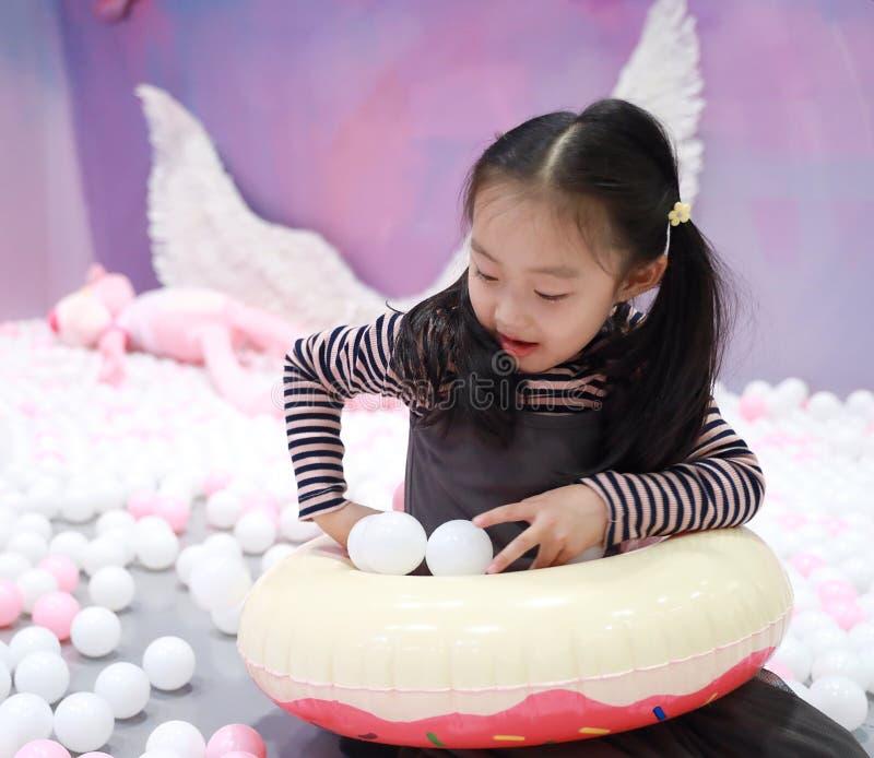 Beautiful cheerful little girl playing pleasure ground on playground stock image