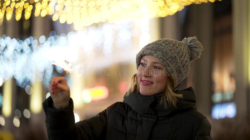 Beautiful, cheerful woman holding sparklers on night, blur city lights background, winter holidays concept. Young royalty free stock photography