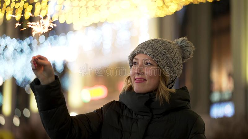Beautiful, cheerful woman holding sparklers on night, blur city lights background, winter holidays concept. Young stock images