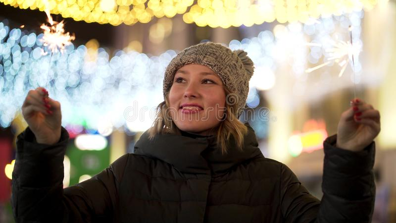 Beautiful, cheerful woman holding sparklers on night, blur city lights background, winter holidays concept. Young stock image