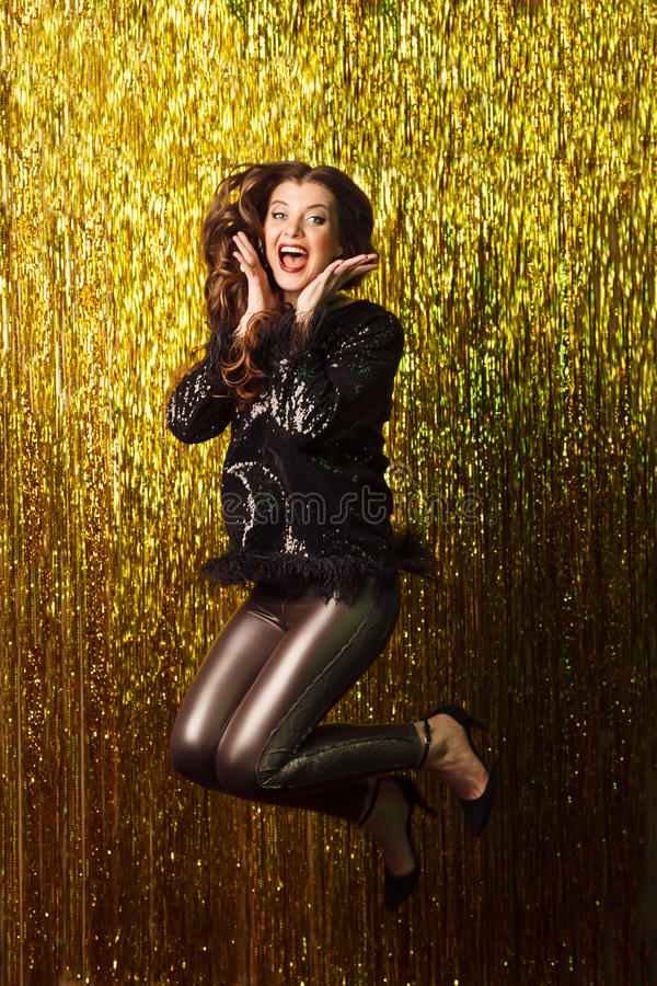 Beautiful cheerful woman jumping on sparkling background. Party. royalty free stock photos