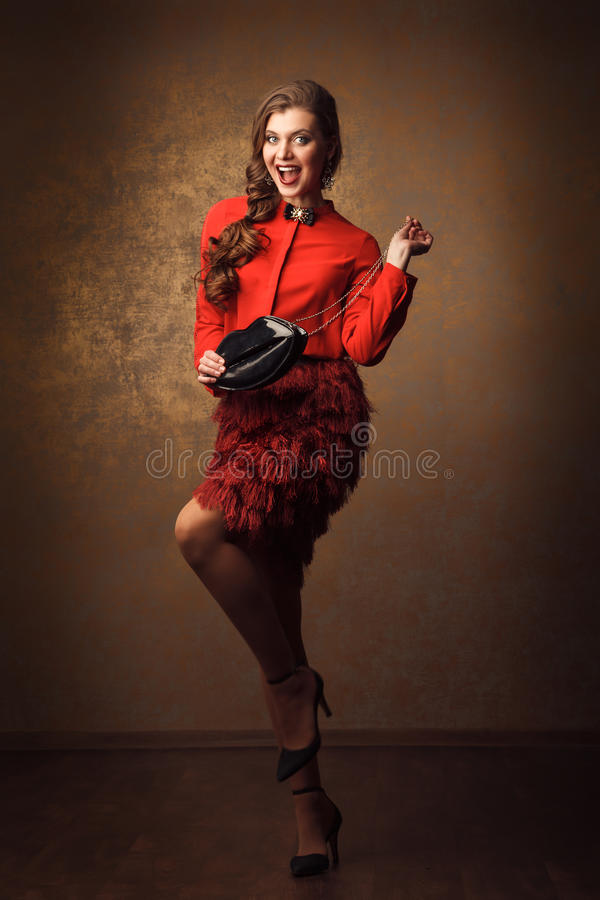 beautiful cheerful woman in red dress with lips shape handbag stock photos