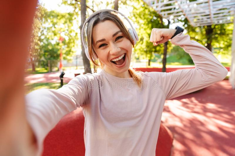 Beautiful cheerful young fitness sports woman posing outdoors in park listening music with earphones take selfie by camera royalty free stock photos