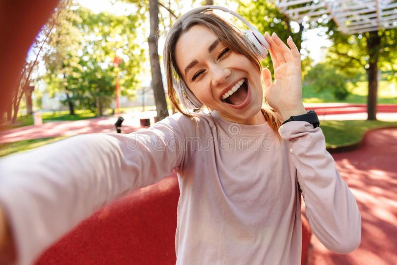 Beautiful cheerful young fitness sports woman posing outdoors in park listening music with earphones take selfie by camera royalty free stock image