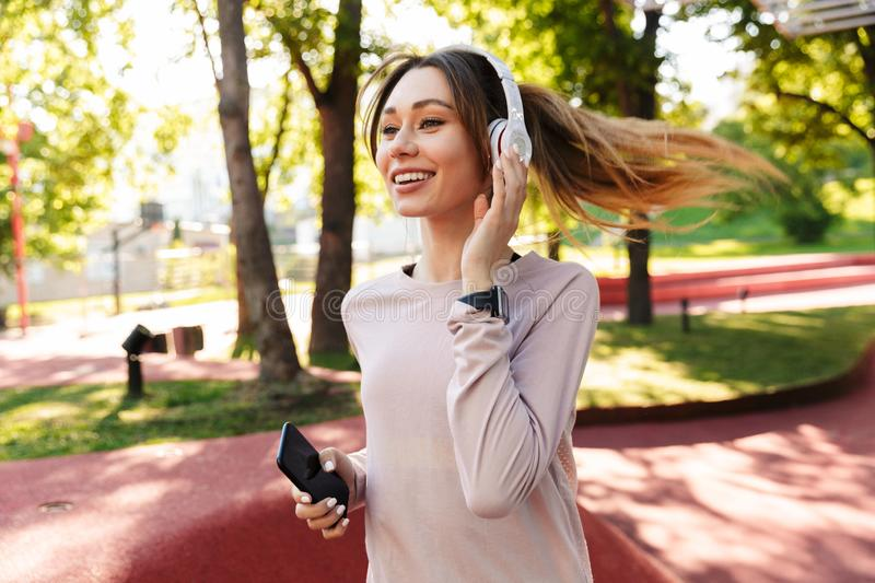 Beautiful cheerful young fitness sports woman posing outdoors in park listening music with earphones using mobile phone royalty free stock image