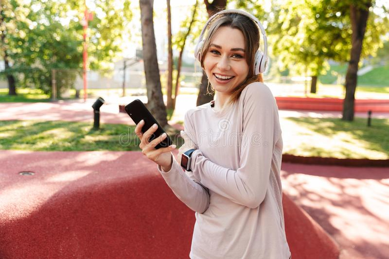 Beautiful cheerful young fitness sports woman posing outdoors in park listening music with earphones using mobile phone royalty free stock photography