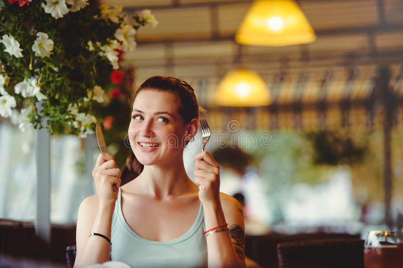 Beautiful cheerful young woman holding fork and knife in a restaurant. Looking at the camera. royalty free stock photos