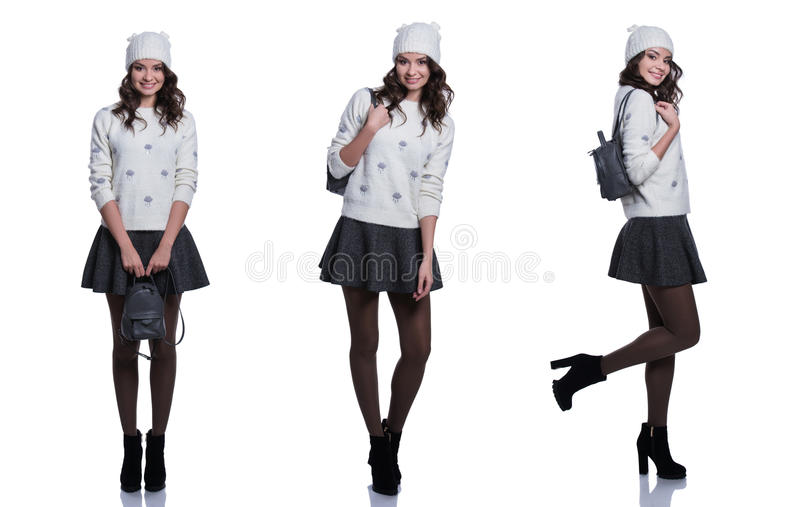 Beautiful cheerful young woman wearing knitted sweater, skirt, hat and backpack. Isolated on white background. royalty free stock images