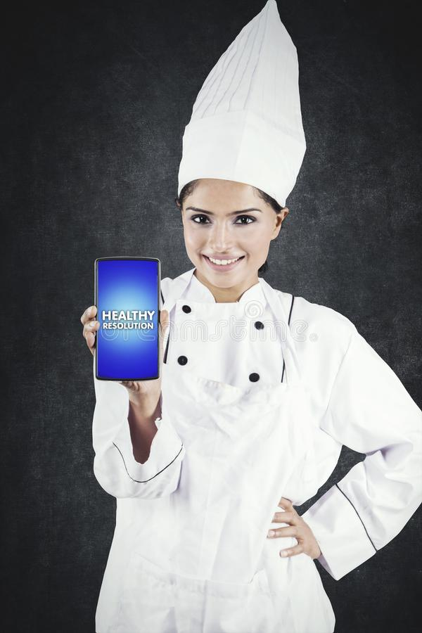 Beautiful chef showing healthy resolution text. Beautiful female chef showing healthy resolution text on a mobile phone while standing in the studio royalty free stock images