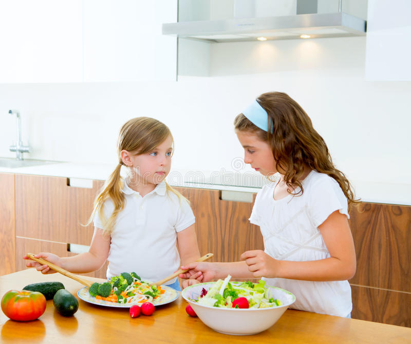 Beautiful chef sisters at kitchen preparing salad royalty free stock photography
