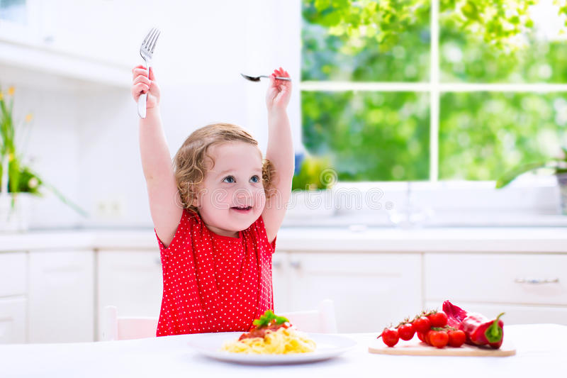 Beautiful child eating pasta. Kids eat pasta. Healthy lunch for children. Toddler kid eating spaghetti Bolognese in a white kitchen at home. Preschooler child royalty free stock photo