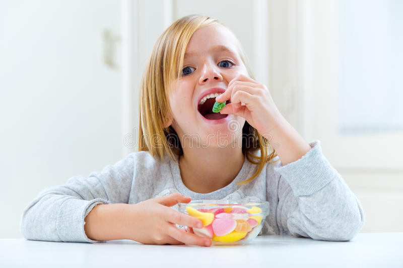Beautiful child eating sweets at home. Portrait of beautiful child eating sweets at home stock image