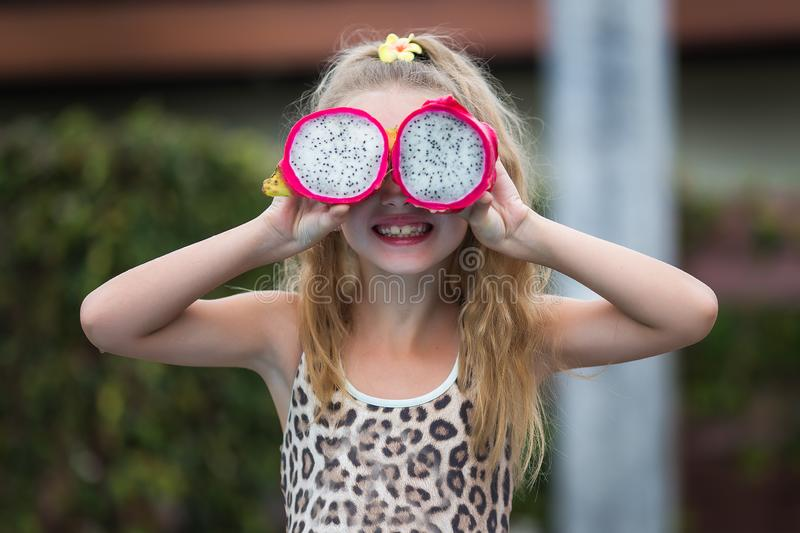 Beautiful child girl playing with dragon fruit near a swimming pool. Tropical outdoor background. Copy space stock photography