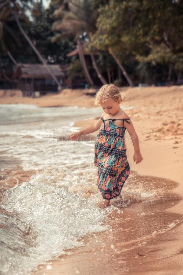 Beautiful child girl playing with waves on beach tropical island during summer holidays concept carefree childhood travel lifestyl royalty free stock image
