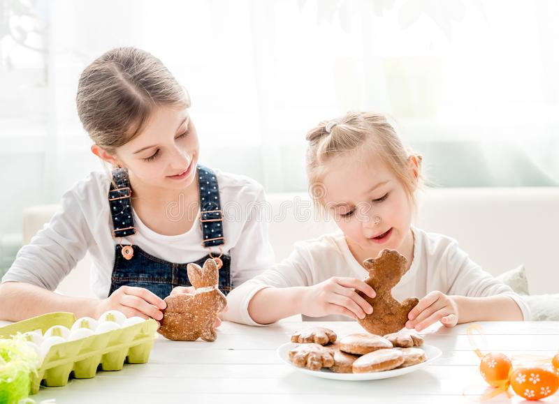 Child girl decorating Easter cookies stock photography