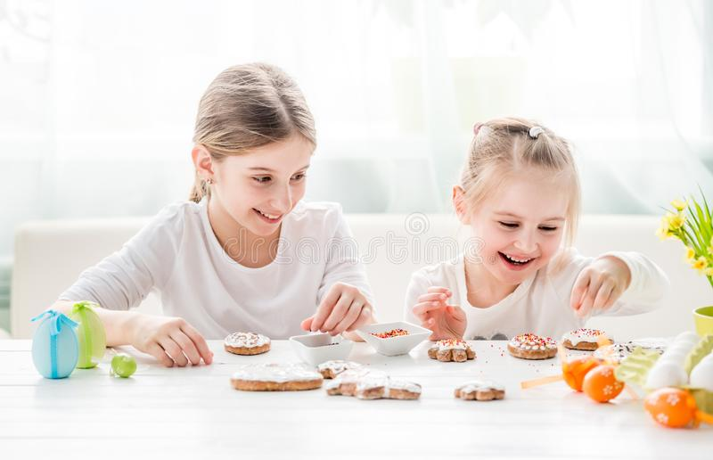 Child girl decorating Easter cookies royalty free stock photos