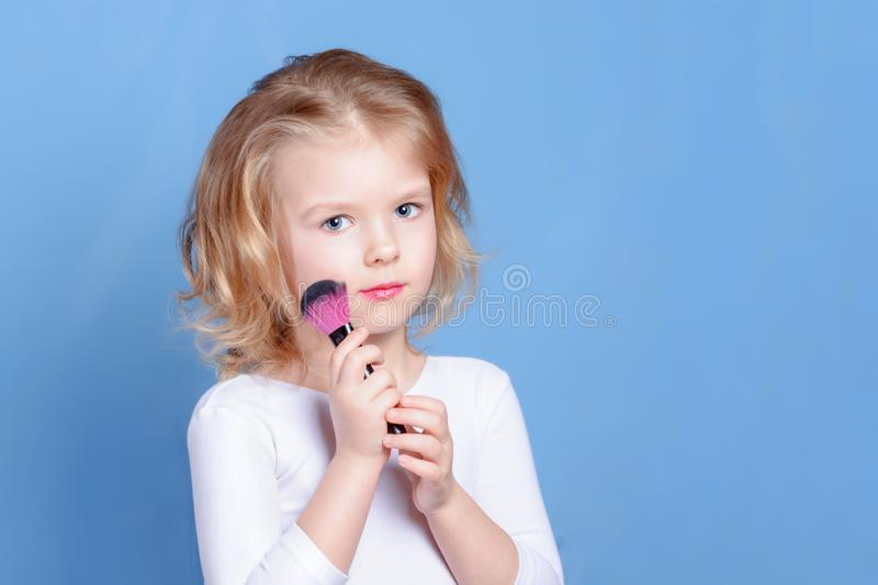 A beautiful child holds a makeup brush in her hand. A small girl with blond hair. Light advertising photo. royalty free stock photography