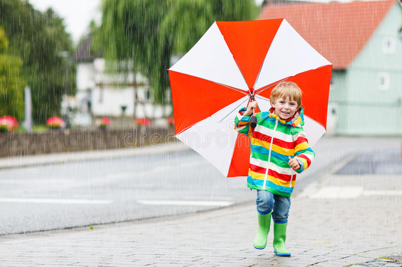 Beautiful child with red umbrella and colorful jacket outdoors a royalty free stock images