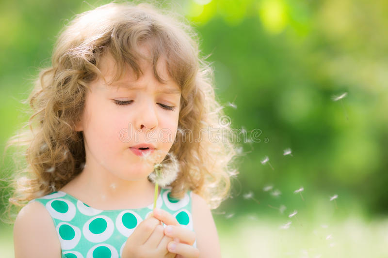 Beautiful child in spring. Beautiful child with dandelion flower in spring park. Happy kid having fun outdoors stock photo