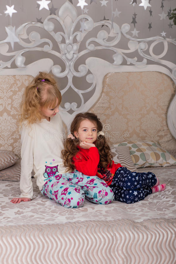 Download Beautiful Children Play In Their Pajamas On The Bed Before Goin Stock Photo - Image: 83719798