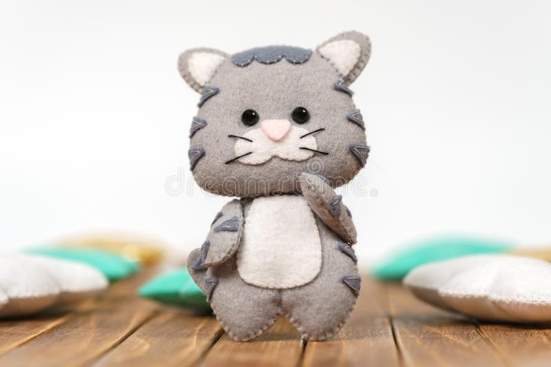 Beautiful children`s toy. Gray kitty made of felt on a wooden background stock image