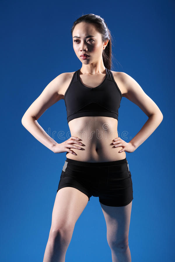 Beautiful Chinese girl warm up fitness exercise. Calf stretch during fitness warm up by beautiful young Chinese girl wearing black sports bra and shorts royalty free stock image