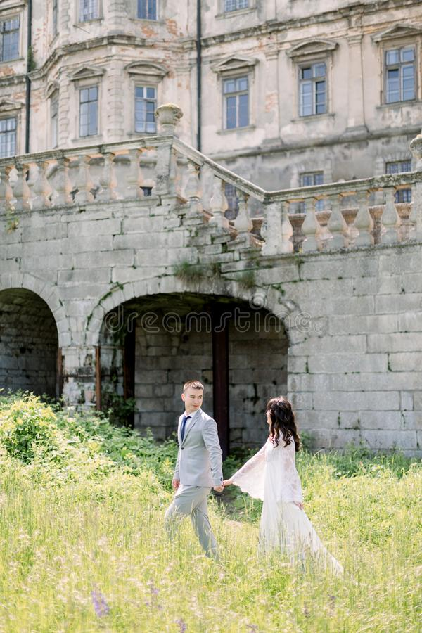 Beautiful Chinese wedding couple are walking near old building, old castle outside, vintage palace outdoor. Amazing royalty free stock photos