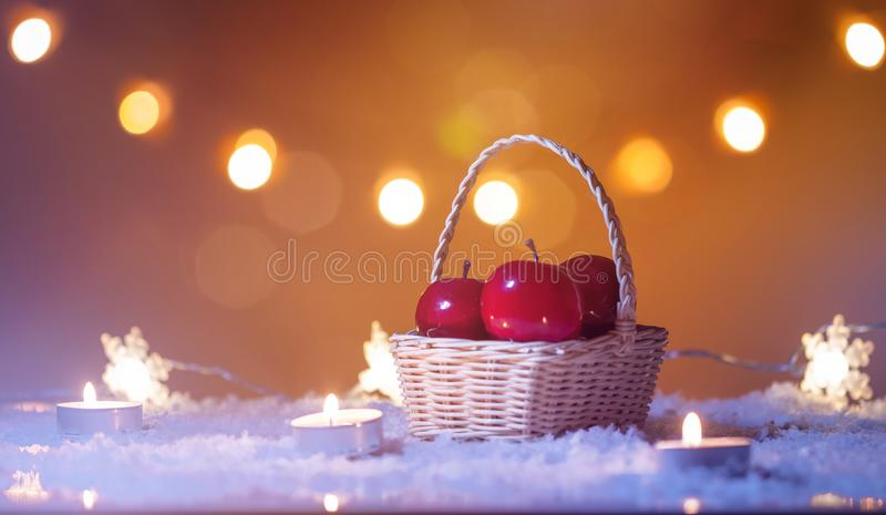 Christmas background with basket of red apples, candles, snow, stars and bokeh lights stock photography