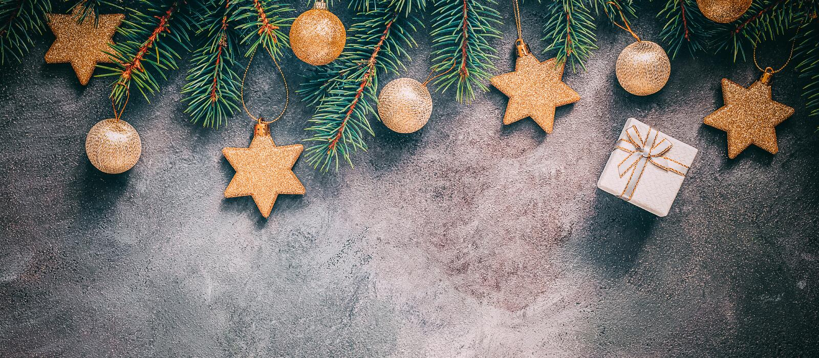 Beautiful Christmas background border. Spruce branches are decorated with gold balls and stars on an abstract rustic background. stock photography